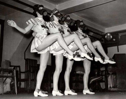 London chorus girls rehearse in their gas masks, 1939.