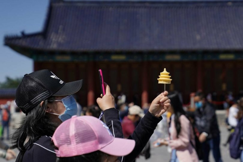 A tourist snaps a picture of her ice cream at the Temple of Heaven in Beijing.
