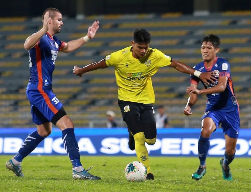 Shahrel Fikri Md Fauzi (tengah) diasak pemain Felda United pada perlawanan Liga Super di Stadium Perak. FOTO SHARUL HAFIZ ZAM.