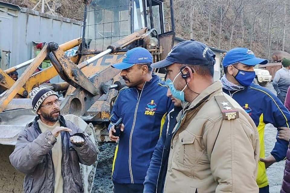 Pekerja bercakap dengan pasukan penyelamat selepas kenaikan air mendadak memusnahkan jambatan dan jalan raya di kampung Reni, daerah Chamoli, Uttarakhand, hari ini. - Foto AFP