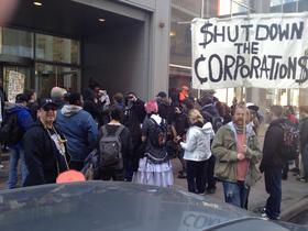 Protesters gather outside 1700 Broadway after marching through the lobby, escorted by police and security guards.