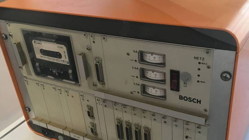 Kiste in der Größe eines Koffers, orange ummantelt, mit zahlreichen Bedienknöpfen vorn.