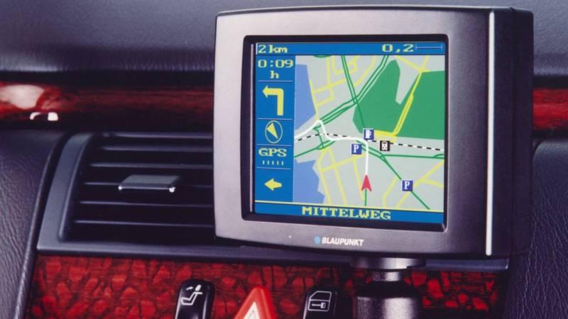 Kleiner Bildschirm eines Navigationssystems mit Landkarte vor Armaturenbrett.