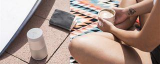 Woman listening to a SoundLink Revolve speaker outside