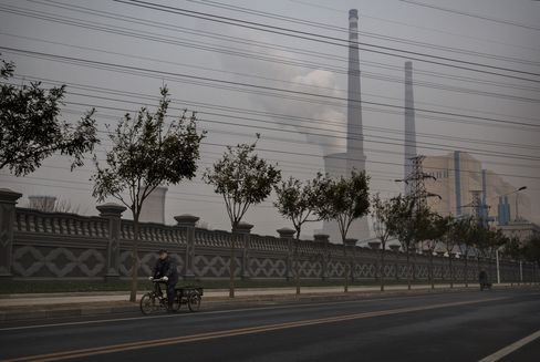 A Chinese man rides a bicylce as a coal fired power plant is seen in the background. Photographer: Kevin Frayer/Getty Images