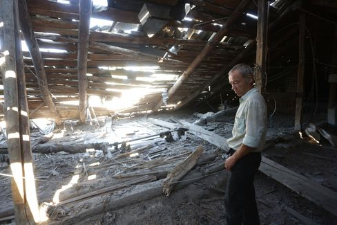 A man examines his destroyed home after shelling between Ukrainian and pro-Russian forces on August 10, 2015 in Ukraine. Photographer: Aleksey Filippov/AFP/Getty Images