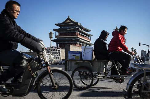 People ride a tricycle and electric bikes past the Zhengyangmen gate in Beijing, China, on Wednesday, Dec. 2, 2015. China's great rebalancing -- the long-sought shift away from investment and manufacturing towards consumption and services -- is one of the nation's big themes of the year. One problem: the rebalancing stops at the water's edge. Photographer: Qilai Shen/Bloomberg