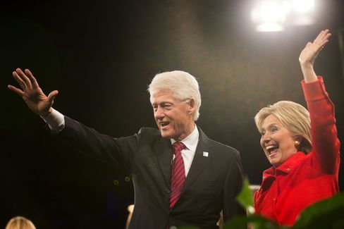 Hillary Clinton waves to supporters with husband Bill Clinton, former U.S. president, at the conclusion of the Jefferson-Jackson Dinner in Des Moines, Iowa, U.S., on Saturday, Oct. 24, 2015.