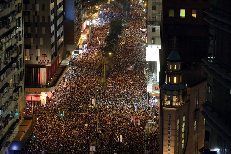 Protesters march at night during a rally in Hong Kong, China, on Sunday, June 16, 2019. Tens of thousands of demonstrators poured into central Hong Kong as organizers remained defiant even after the city's leader suspended consideration of the China-backed extradition plan that sparked some of the biggest protests in the city in decades.
