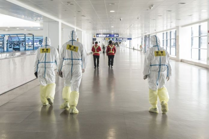 Airport employees wear full body protective suits at Pudong International Airport in Shanghai on March 28.
