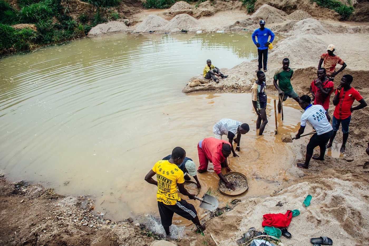 A crew in Kono District sifts through mud and rocks in search of diamonds. The diggers are paid $2.50 a day