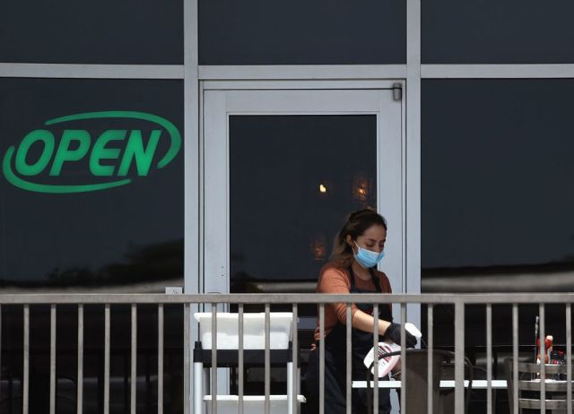 A restaurant employee cleans a outdoor patio table at Benny's Cafe prior to the Texas' scheduled reopening of businesses during the coronavirus (COVID-19) pandemic on April 27, 2020 in Colleyville, Texas.