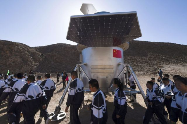 Students walk past a model of a lander.