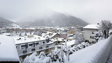 Mist covers the mountain as snow sits on commercial and residential property below in Davos, Switzerland, on Tuesday, Jan. 12, 2015.