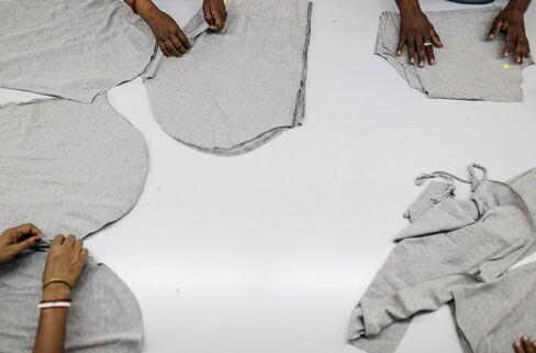 Employees fold cotton fabric.