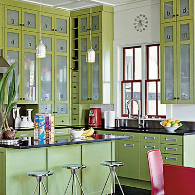In this beach kitchen, avocado green cupboards with frosted glass fronts have decorative letters etched into the top sections. Black countertops compliment green shades in the kitchen.