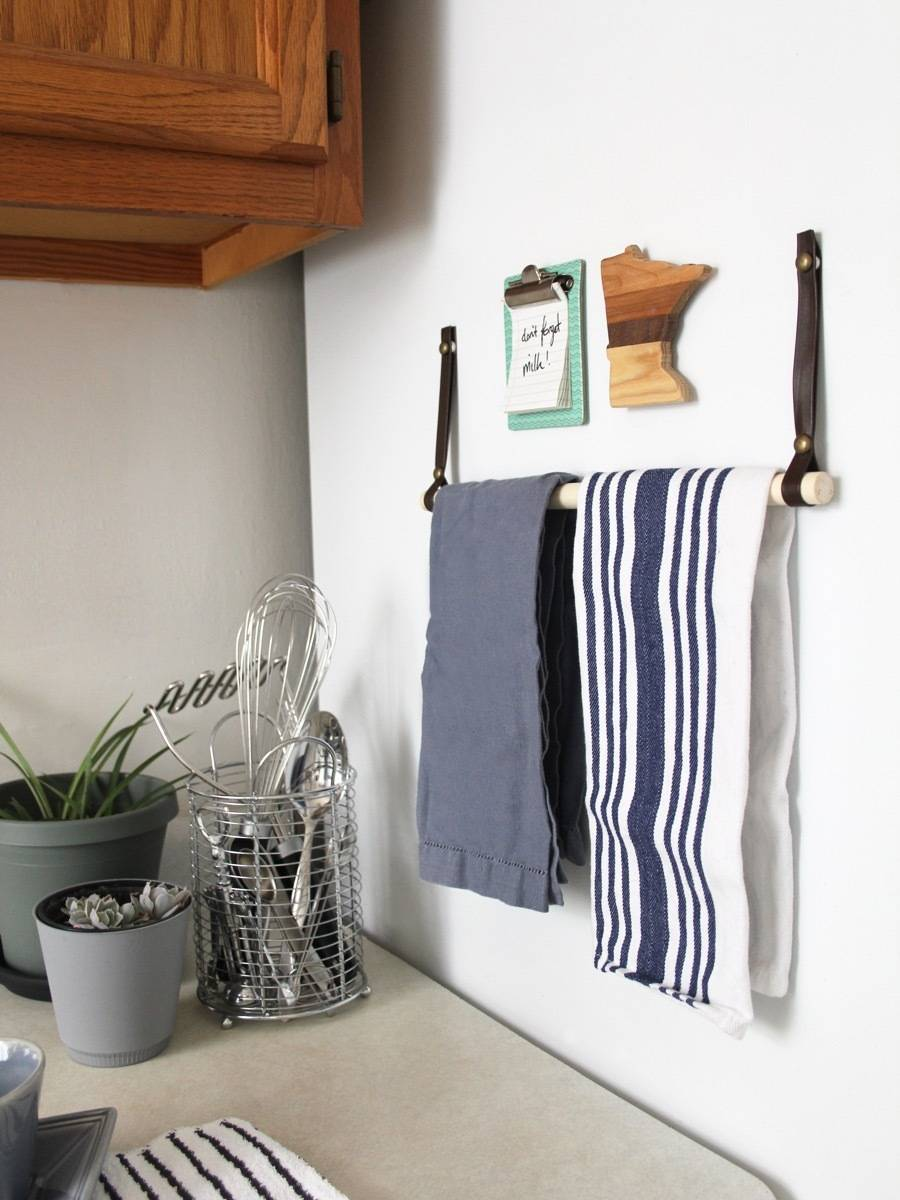 Save storage space and go vertical! Use the side of the fridge to store towels with this DIY towel bar.