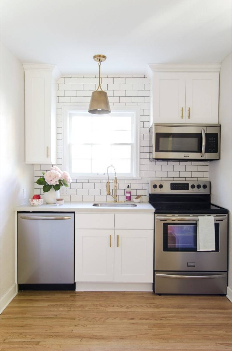 Kitchen, after - stainless steel appliances, gold accents, subway tile with black grout