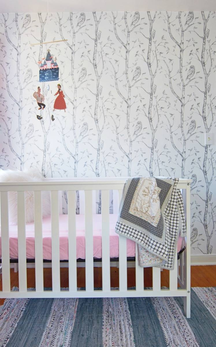 Crib with mobile and tree wallpaper