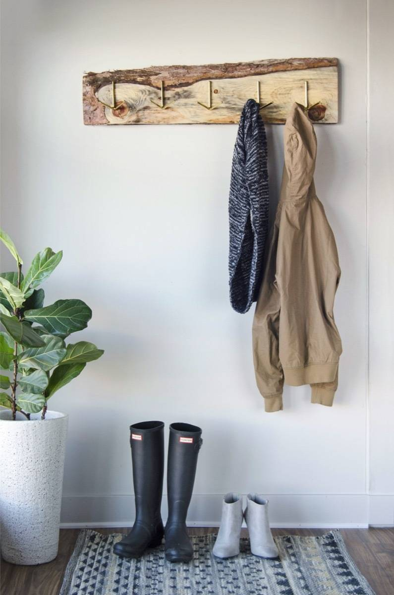 An old, discarded board gets new life as a rustic DIY coat rack