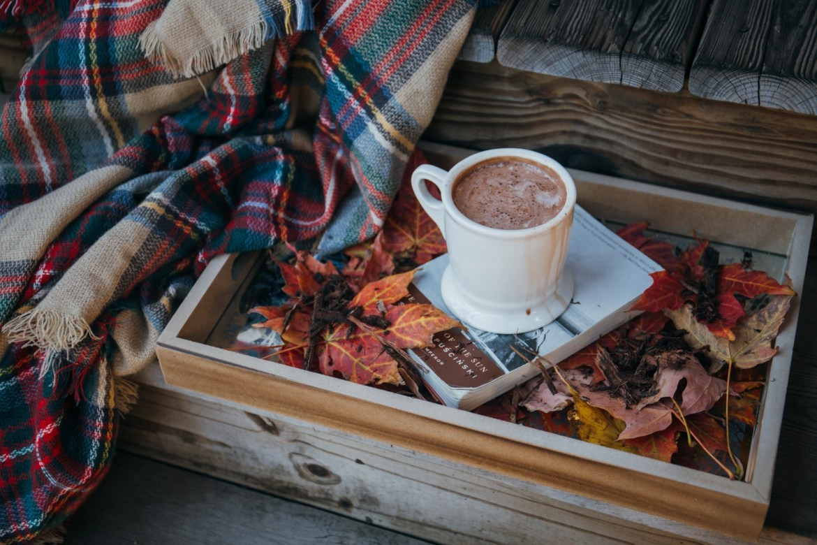 A cozy fall scene with a plaid blanket, hot chocolate, and fall leaves on a wood tray