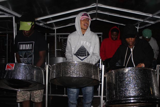 Steel pan drummers (from left) Michael Edwards, 20, Jordan Cato, 17, and Kaila Charles, 16, play in the rain at practice for the Panorama tournament on Saturday.