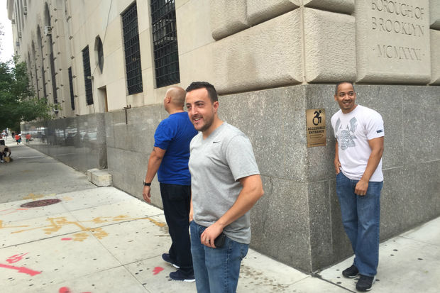 Three agents with Immigration and Customs Enforcement wait outside Brooklyn Criminal Court on Sept. 14.