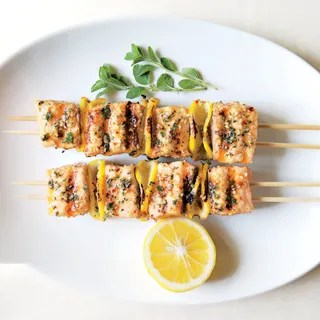 Two salmon kebabs on wooden skewers on a platter with a lemon half for sqeezing.