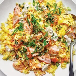 flaked salmon atop a mound of golden fried rice sprinkled with scallions