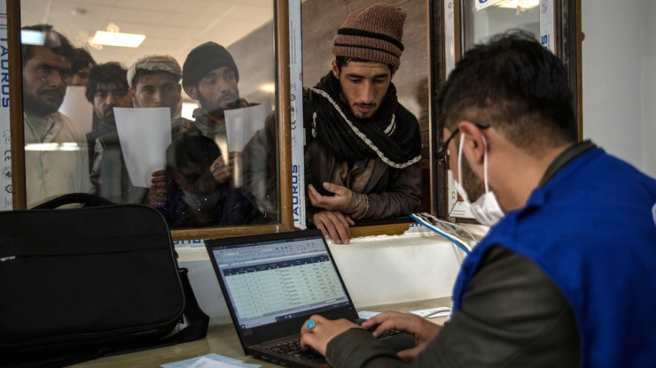 An IOM staff member registers newly arrived returnees at the border reception centre.