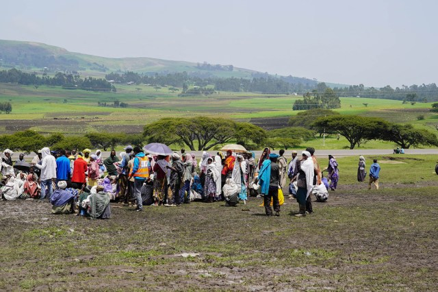 A group of internally displaced people wait on an arid landscape to receive aid in the town of Dabat.