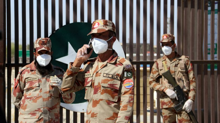 Paramilitary soldiers wear face masks as they stand in front of a closed gate at Pakistan's border post in Taftan.