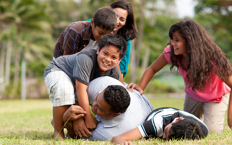 A family play football together in a park living the word of wisdom