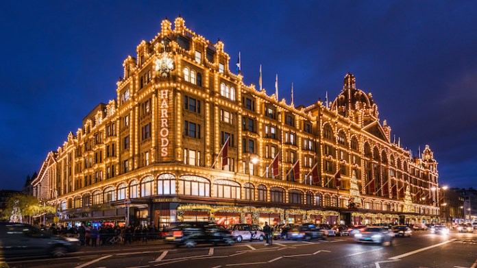The exterior or Harrods department store in Knightsbridge, London, lit up for Christmas with thousands of golden lights