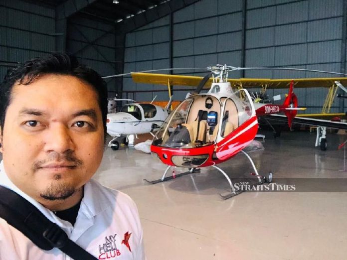 Mohd Irfan posing in front of a red livery G2CA helicopter. - NSTP/ courtesy of Lt Col Muhammad Haris Asmuni