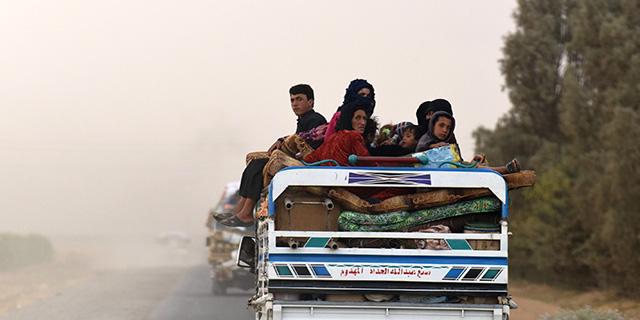 Displaced Syrians from Deir Ezzor head to refugee camps on the outskirts of Raqqa on Sept. 24 as Syrian fighters backed by U.S. special operations forces battle to capture ISIS's last remaining stronghold. (Bulent Kilic/AFP/Getty Images)