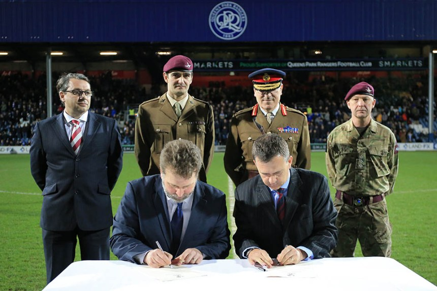Defence Minister Mark Lancaster signing the Armed Forces covenant with QPR's CEO Lee Hoos. Photograph by Back Page Images.