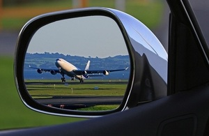 An aeroplane taking off reflected in the side mirror of a car