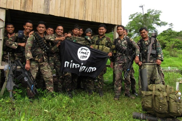 SMALL VICTORY.This photo taken on June 3 shows Philippine soldiers displaying the flag used by the Islamic State group after overrunning a militant camp at a remote village in Butig town, Lanao del Sur province after a 10-day battle. Photo by Richelle Umel/ AFP