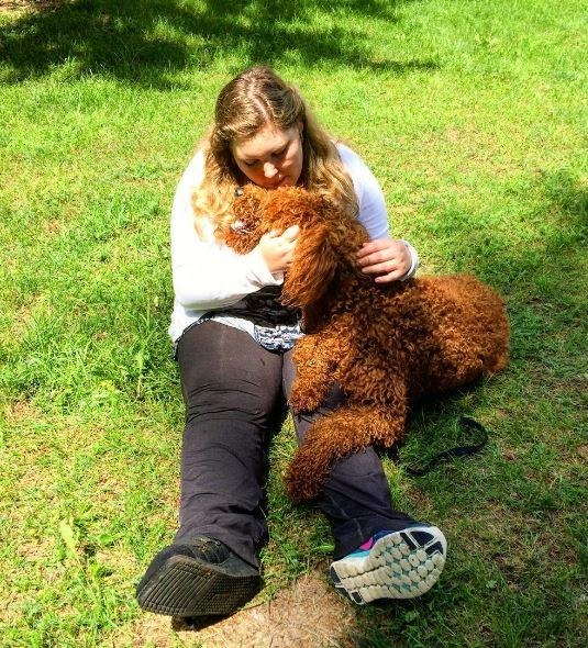 woman hugging service dog on grass