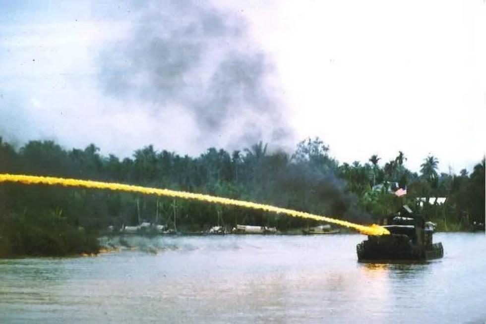 An American riverine patrol employs its flamethrower in Vietnam.
