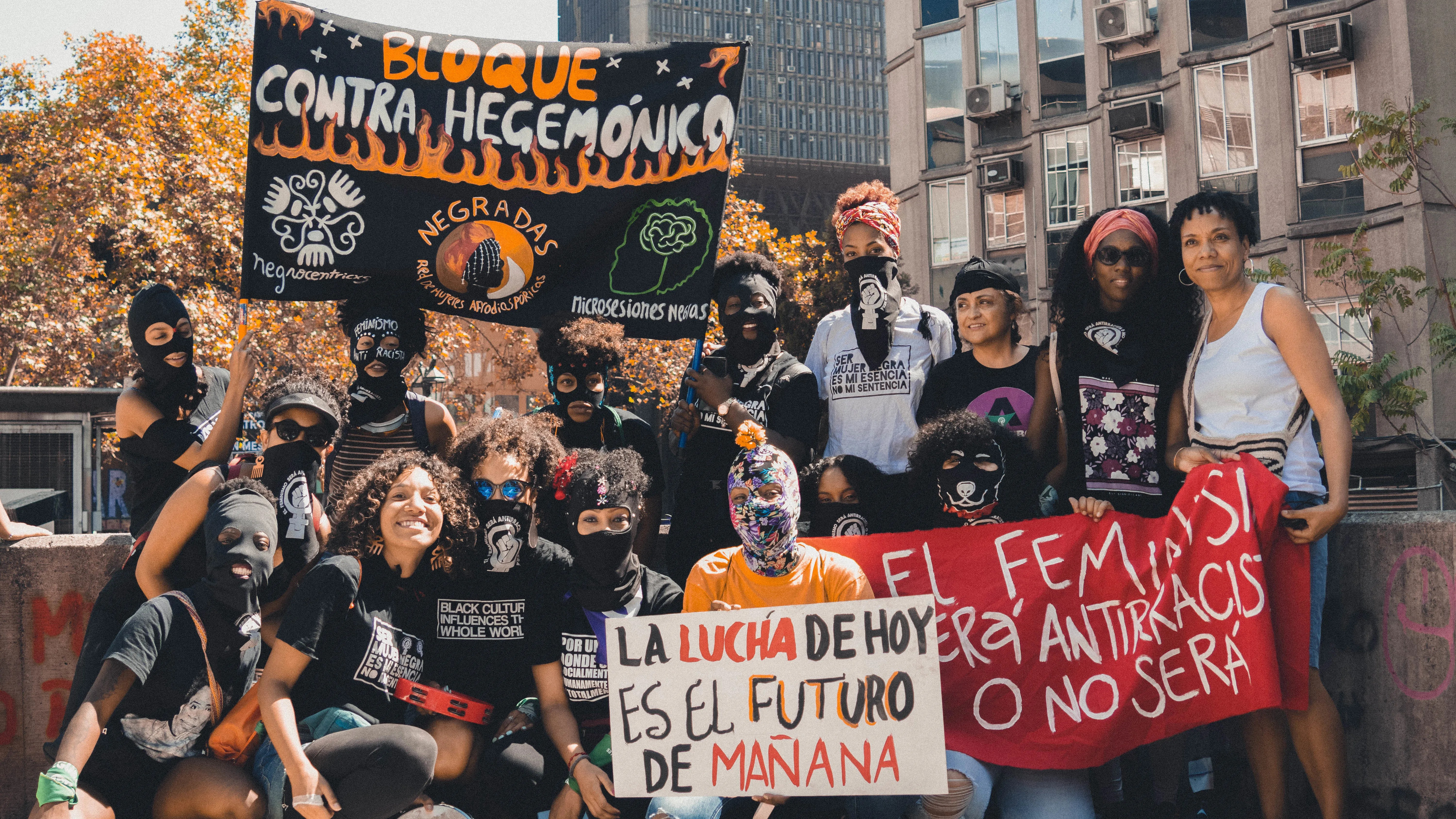 Black Chilean feminists holding signs, wearing masks, and protesting racism.