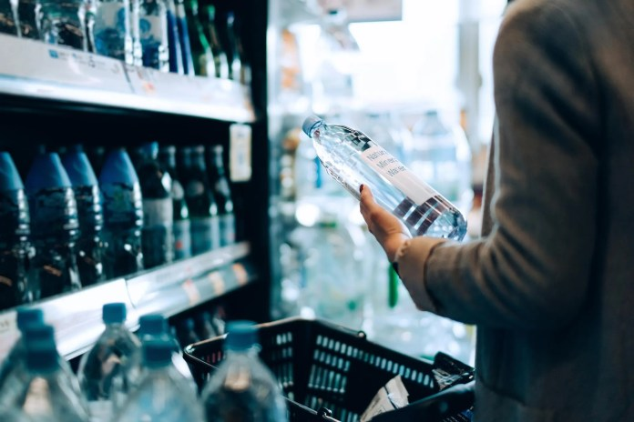 Close up of woman with shopping cart shopping for bottled water along the beverage aisle in a supermarket