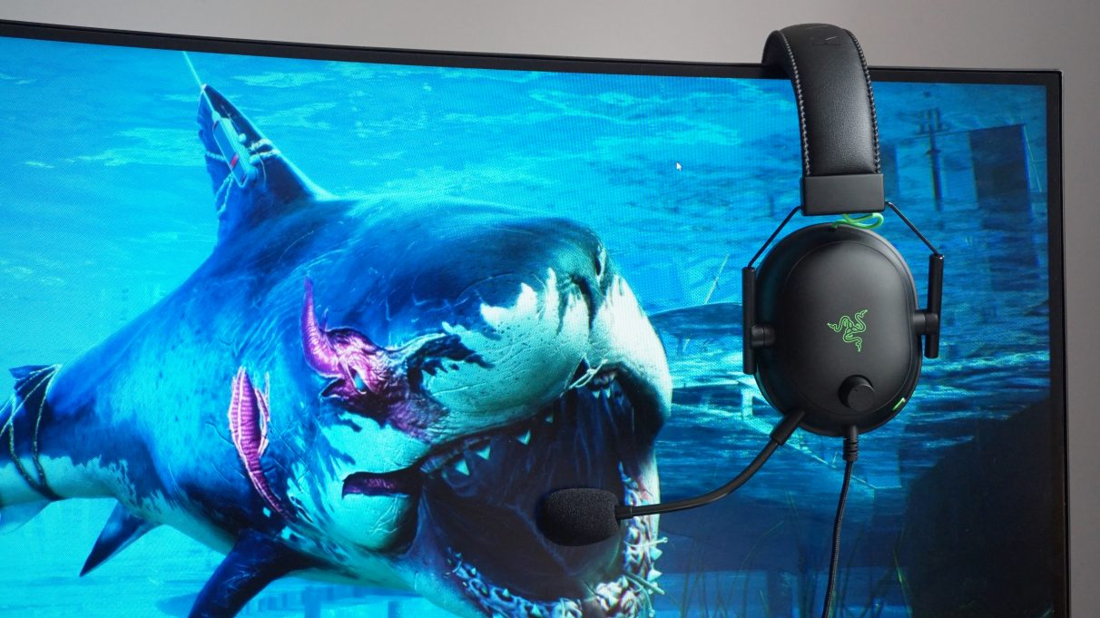 A photo of the Razer Blackshark V2 hanging down on one side of a monitor with a wallpaper of a big shark on it.
