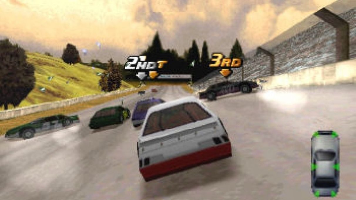 An image from Destruction Derby 2 which shows a red and white race car amidst a cluster of other race cars. Two have crashed, with debris flying onto the track, while two others power towards the finish line.