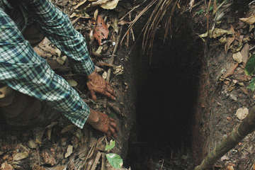FUNAI field workers find a hole dug in the Amazon forest by uncontacted indian 'Last of his tribe', which he used to trap animals when hunting. Tanaru territory, Rondônia state, Brazil.