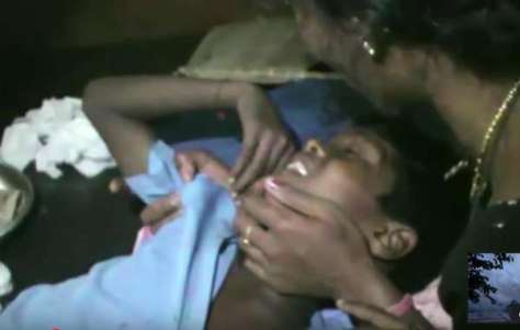 Akash Orang is comforted by his mother after being shot by a park guard. He is now severely disabled.