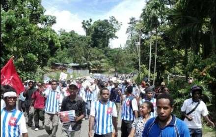 """Papuasi marciano per l'indipendenza indossando le t-shirt con la bandiera della """"Stella del mattino""""."""