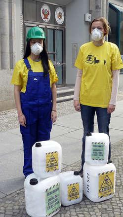 Dos manifestantes en Berlín con máscaras de gas y cascos denuncian los efectos letales del proyecto Camisea para los indígenas aislados.