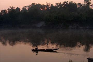 Un uomo Pirahã sul fiume al tramonto.